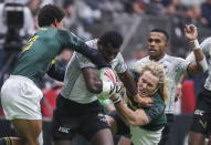 Fiji's Meli Derenalagi (6) runs with the ball against Kurt-Lee Arendse, left, during World Rugby Sevens Series game action in Vancouver, British Columbia, Sunday, March 10, 2019. (Ben Nelms/The Canadian Press via AP)
