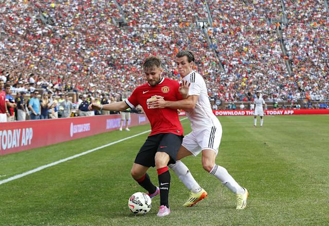 Manchester United defender Alexander Buttner, left, protects the ball from Real Madrid midfielder Gareth Bale during a Guinness International Champions Cup soccer match at Michigan Stadium in Ann Arbor, Mich., Saturday, Aug. 2, 2014. Manchester United won 3-1. (AP Photo/Paul Sancya)