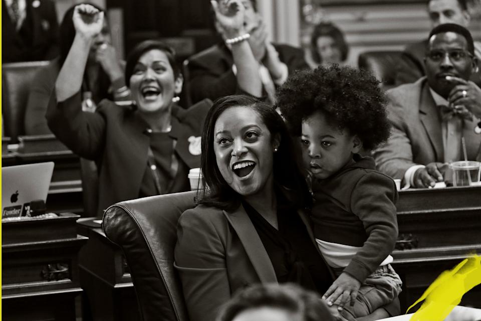 Del. Jennifer Carroll Foy holds her son, Alex Foy, as she and Del. Hala Ayala, D-Prince William, back, celebrate the passage of the Equal Rights Amendment in the House chambers at the Capitol, Jan. 27, 2020, in Richmond, Va.