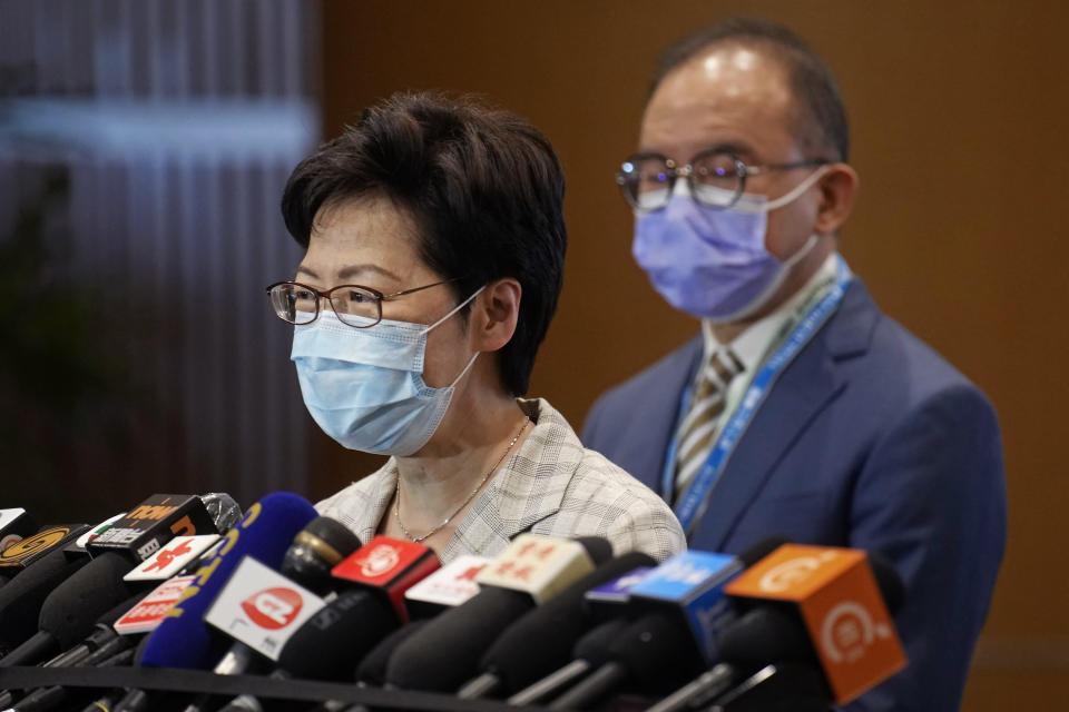 """Hong Kong Chief Executive Carrie Lam, left, speaks, with Erick Tsang, Secretary for Constitutional and Mainland Affairs Bureau, behind her, during a press conference at a polling center for the election committee in Hong Kong Sunday, Sept. 19, 2021. Hong Kong's polls for an election committee that will vote for the city's leader kicked off Sunday amid heavy police presence, with chief executive Carrie Lam saying that it is """"very meaningful"""" as it is the first election to take place following electoral reforms. (AP Photo/Vincent Yu)"""