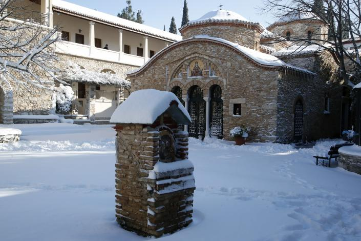 A Greek Orthodox monk walks at Penteli Monastery after a snowfall in northern Athens, Tuesday, Jan. 8, 2019. Schools will remain closed across many parts of the country as a new cold weather front brings freezing temperatures and heavy snowfall. (AP Photo/Thanassis Stavrakis)