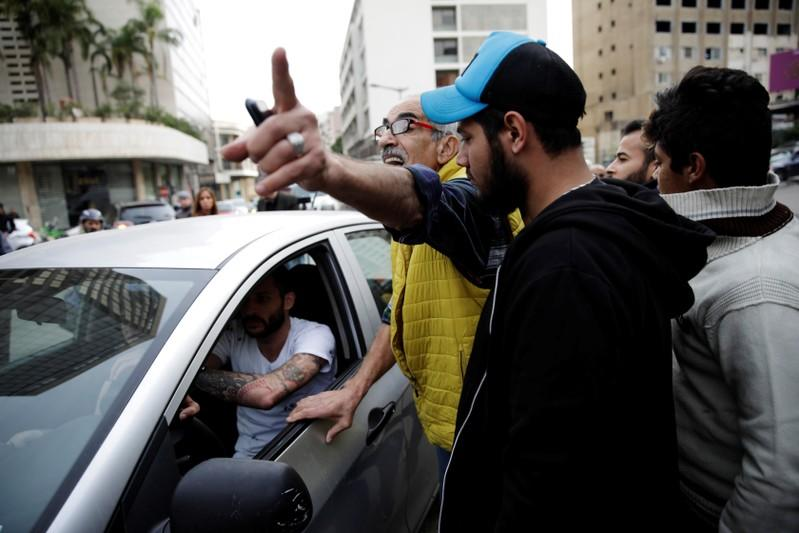 A protester gives directions to fellow protesters to open a roadblock for a driver during ongoing anti-government demonstrations in Beirut