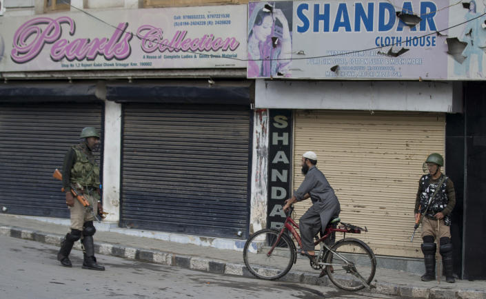 A Kashmiri cyclist rides past Indian Paramilitary soldiers as they stand guard during curfew in Srinagar, Indian controlled Kashmir, Wednesday, Aug. 7, 2019. Authorities in Hindu-majority India clamped a complete shutdown on Kashmir as they scrapped the Muslim-majority state's special status, including exclusive hereditary rights and a separate constitution, and divided it into two territories. (AP Photo/Dar Yasin)