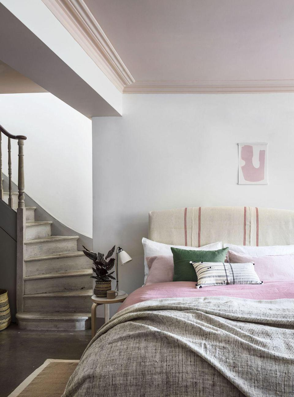 <p>A white, pink and grey bedroom colour scheme can work wonders too. Here the ceiling, which has been painted pale pink, really helps to zone this sleeping space. The bedlinen, layered with a slightly punchier pink shade and grey marl sheets, along with the green cushion and the play on textures and patterns, creates a wonderfully calm and relaxing bedroom.</p>