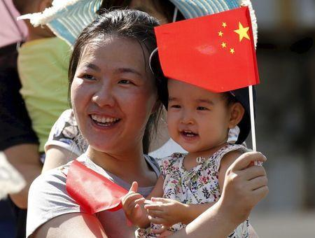 A woman and her baby wait on the street for a military parade marking the 70th anniversary of the end of World War Two, in Beijing, September 3, 2015. REUTERS/Kim Kyung-Hoon/Files