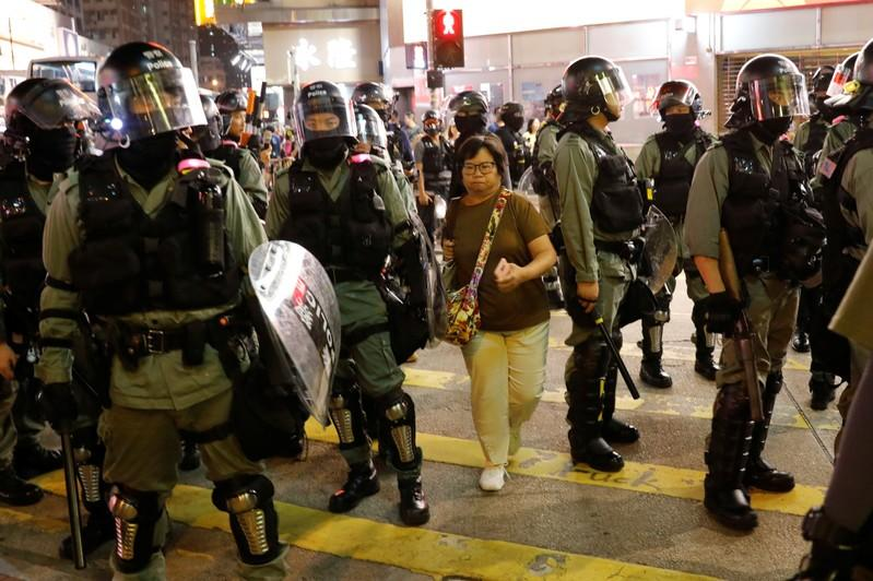 A woman makes her way between riot police officers as they try to disperse protesters gathering for a demonstration in Hong Kong