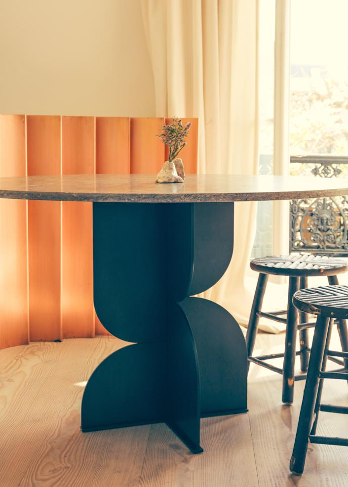 """<div class=""""caption""""> The screen in the background is by Champsaur for Pouenat Ferronnier, as is the steel table with a travertine top. The chestnut stools are custom. </div>"""