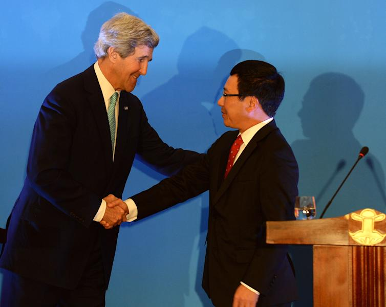 U.S. Secretary of State John Kerry, left, shakes hands with Vietnamese Foreign Minister Pham Binh Minh after a joint press conference in Hanoi Monday, Dec. 16, 2013. Taking clear aim at China's growing aggressiveness in territorial disputes with its smaller neighbors, U.S. Secretary of State Kerry announced Monday that the United States will boost maritime security assistance to the countries of Southeast Asia amid rising tensions with Beijing. (AP Photo/Hoang Dinh Nam, Pool)