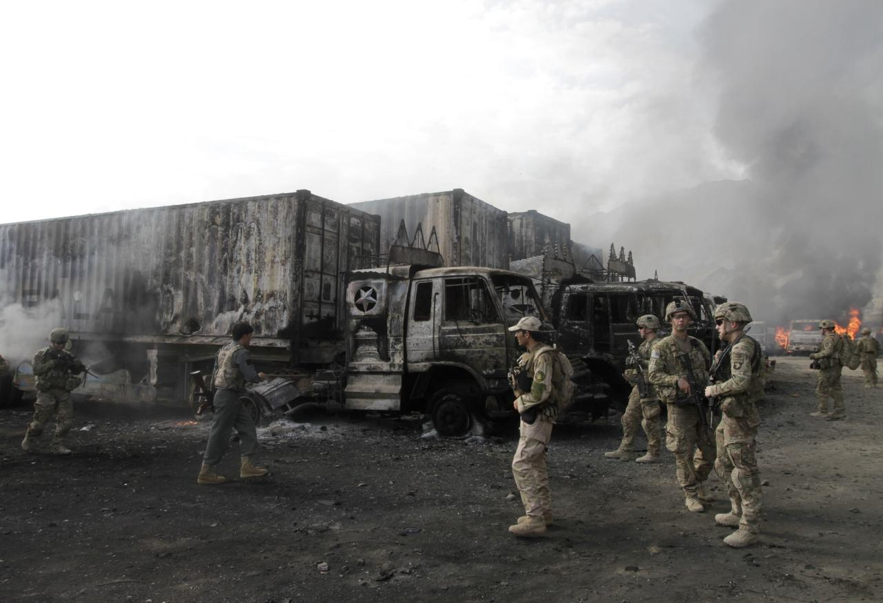NATO troops walk near burning NATO supply trucks after, what police officials say, was an attack by militants in the Torkham area near the Pakistani-Afghan in Nangarhar Province June 19, 2014. According to officials on Thursday, at least 37 trucks belonging to NATO forces were destroyed after three suicide bombers targeted the NATO supply trucks, with two civilians wounded in the attack. REUTERS/ Parwiz (AFGHANISTAN - Tags: CIVIL UNREST MILITARY POLITICS)