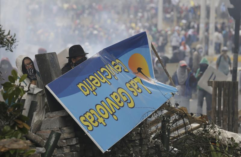 Anti-government demonstrators use a sign for cover at a barricade during clashes with police in Quito, Ecuador, Saturday, Oct. 12, 2019. Protests, which began when President Lenin Moreno's decision to cut subsidies led to a sharp increase in fuel prices, have persisted for days. (AP Photo/Fernando Vergara)