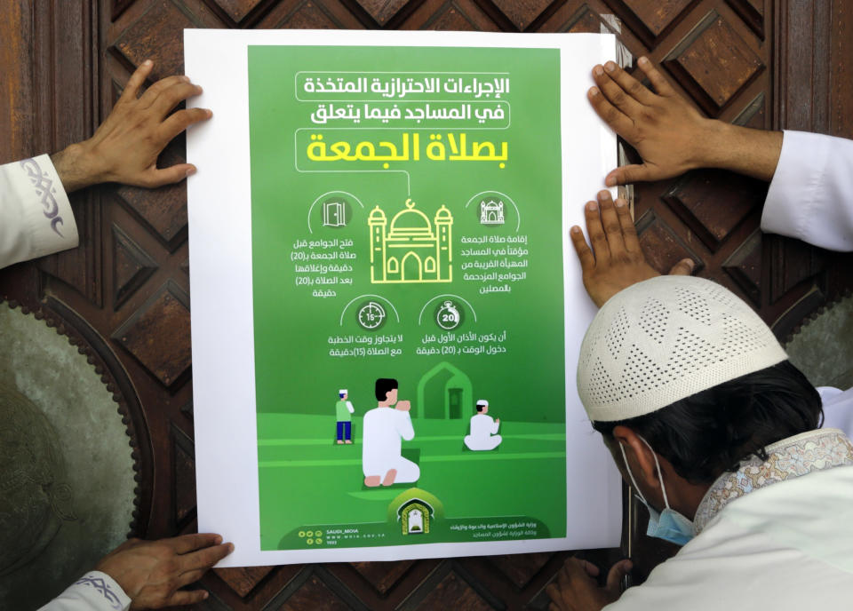 "Workers place a poster with Arabic reads, ""the precautionary measures and instructions inside mosques for Friday prayers"" at al-Mirabi Mosque in Jiddah, Saudi Arabia, Thursday, May 28, 2020. The Ministry of Islamic Affairs said mosques will open to the public for prayers from May 31 until June 20, except in Mecca, with precautionary measures and instructions. (AP Photo/Amr Nabil)"