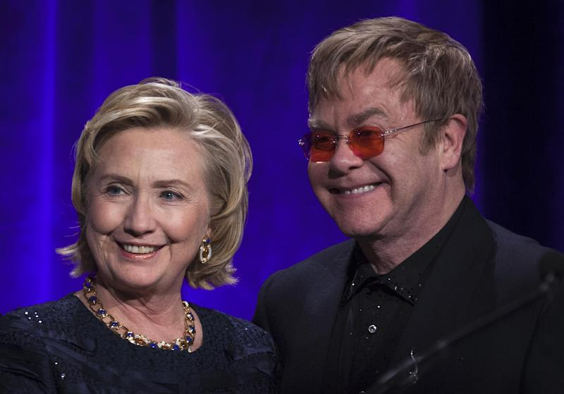 "Former Secretary of State Hillary Clinton, left, poses onstage for a photograph with Elton John after receiving her Founders award during the Elton John AIDS Foundation's 12th Annual ""An Enduring Vision"" benefit gala at Cipriani Wall Street on Tuesday, Oct. 15, 2013, in New York. (Photo by Carlo Allegri/Invision/AP)"