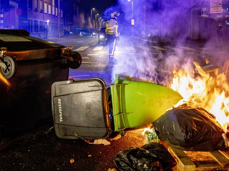 A view of a burning dumpster and other waste containers as a police officer keeps watch in the Schilderswijk neighborhood in The Hague, the Netherlands: EPA