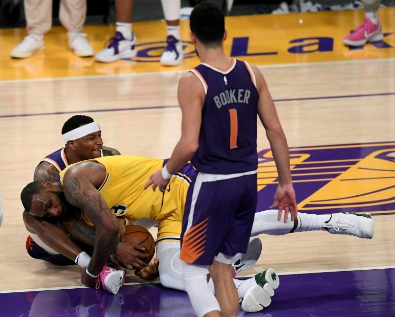 Los Angeles star LeBron James and Phoenix's Torrey Craig tussle for the ball in the Suns' series-clinching victory over the Lakers in game six of their NBA Western Conference 1st-round clash