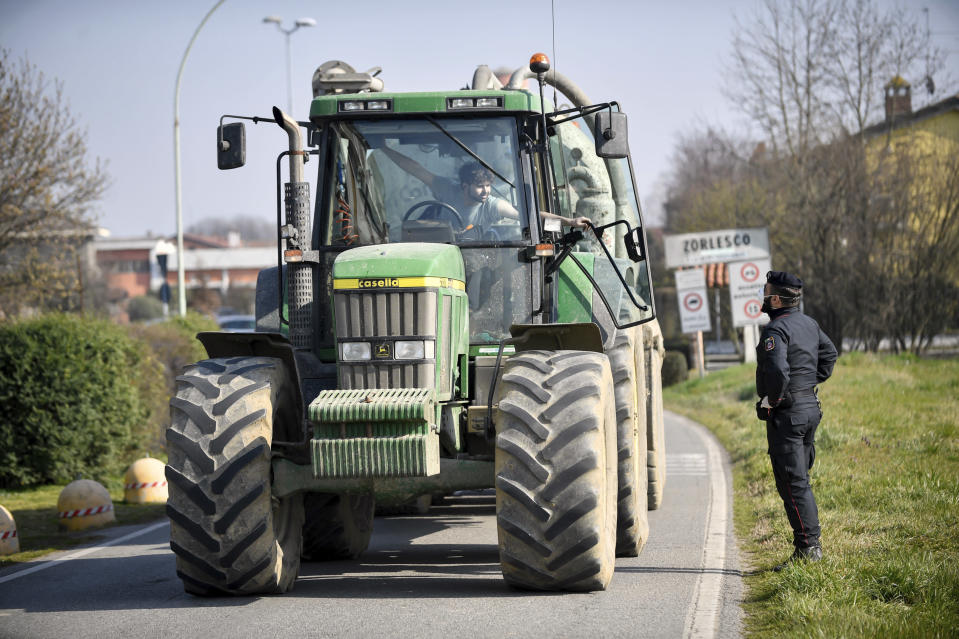 A Carabinieri (Italian paramilitary police) officer talks to a farmer on a tractor at a road block in Zorlesco, Northern Italy, Monday, Feb. 24, 2020. Italy scrambled to check the spread of Europe's first major outbreak of the new viral disease amid rapidly rising numbers of infections. Road blocks were set up in at least some of 10 towns in Lombardy at the epicenter of the outbreak, to keep people from leaving or arriving. (Claudio Furlan/Lapresse via AP)