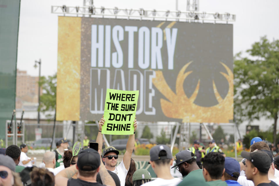 A fan holds up a sign before a parade celebrating the Milwaukee Bucks' NBA Championship basketball team Thursday, July 22, 2021, in Milwaukee. The Bucks defeated the Phoenix Suns 105-98 in Game 6 on Tuesday. (AP Photo/Aaron Gash)