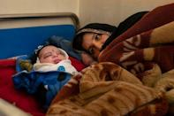 A mother with her newborn rests at the Tangi Saidan clinic (AFP/Elise BLANCHARD)
