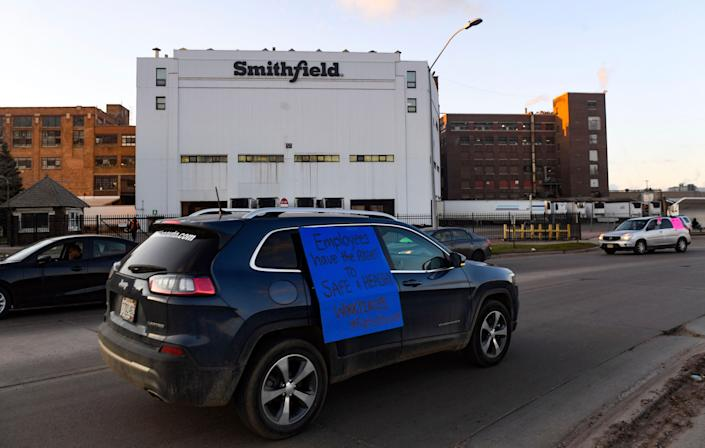 A car sporting a sign calling for a safe and healthy workplace drives past Smithfield Foods in Sioux Falls, S.D., on April 9, 2020, during a protest on behalf of employees after many workers complained of unsafe working conditions amid the COVID-19 outbreak.
