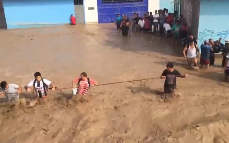 Residents cling to a rope to cross the flooded road to safety