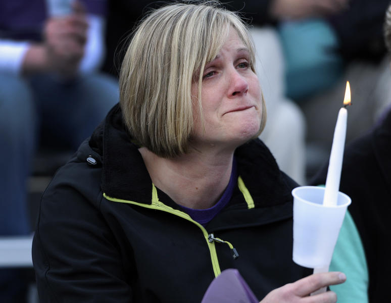 A woman cries during a vigil for Maren Sanchez at Jonathan Law High School, Monday, April 28, 2014, in Milford, Conn. Sanchez was fatally stabbed inside the school on Friday hours before her junior prom. (AP Photo/Jessica Hill)