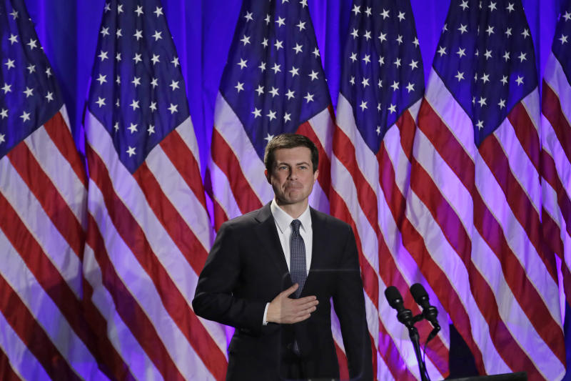 Pictured: Pete Buttigieg at a campaign event in 2019, in front of American flags.
