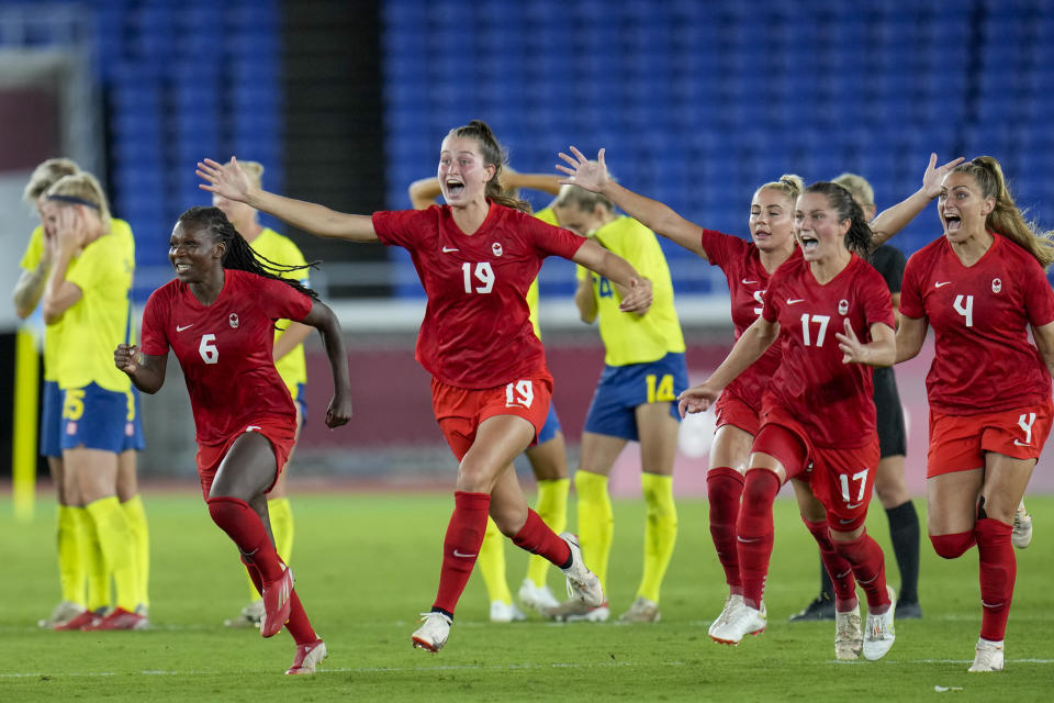 Players of Canada celebrate beating Sweden in a penalty shootout during the women's soccer match for the gold medal at the 2020 Summer Olympics, Friday, Aug. 6, 2021, in Yokohama, Japan. (AP Photo/Fernando Vergara)