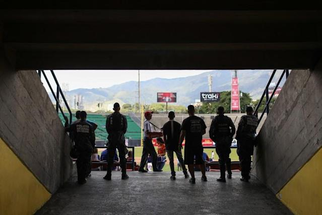 Police officers watch a baseball game at University Stadium in Caracas