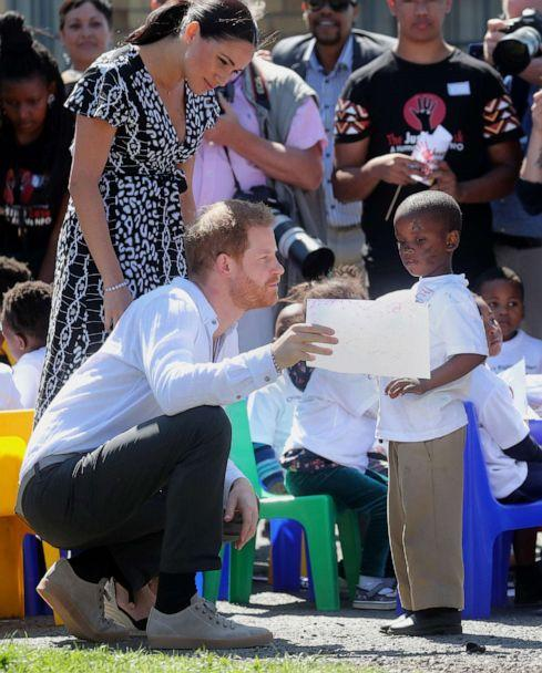 PHOTO: Meghan, Duchess of Sussex and Prince Harry, Duke of Sussex talk with a young boy during a visit to a Justice Desk initiative in Nyanga township, during their royal tour of South Africa, Sept. 23, 2019 in Cape Town. (Chris Jackson/Getty Images)