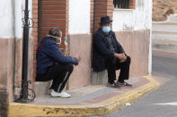 Two men wearing face masks to protect against the spread of coronavirus sit and talk on a street corner in the rural village of La Puerta de Segura, Jaen, Spain, Tuesday, Oct. 27, 2020. Despite overnight curfews, mobility curbs affecting at least four regions and other restrictions, health authorities in Spain are warning that sharp outbreaks of Covid-19 are already straining hospitals. (AP Photo/Paul White)
