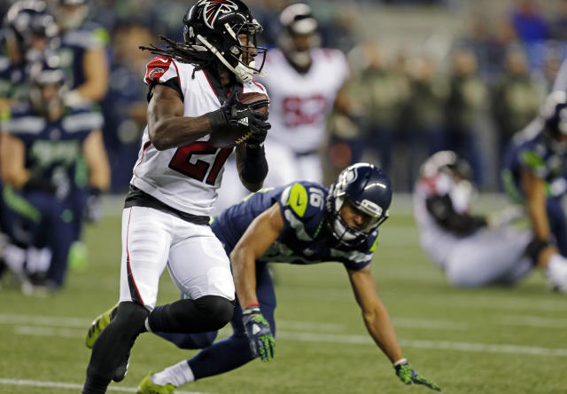 Atlanta Falcons' Desmond Trufant (21) runs with the ball after intercepting it as Seattle Seahawks' Tyler Lockett tumbles behind in the first half of an NFL football game, Monday, Nov. 20, 2017, in Seattle. (AP Photo/Stephen Brashear)