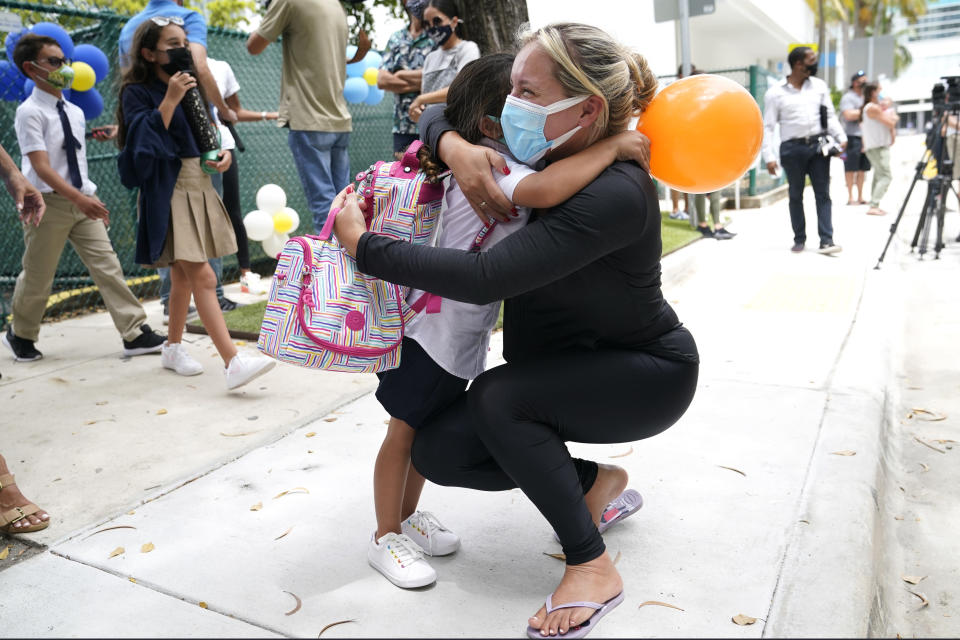 Carol Basilio, right, hugs her daughter Giovanna outside of iPrep Academy on the first day of school, Monday, Aug. 23, 2021, in Miami. Schools in Miami-Dade County opened Monday with a strict mask mandate to guard against coronavirus infections. (AP Photo/Lynne Sladky)