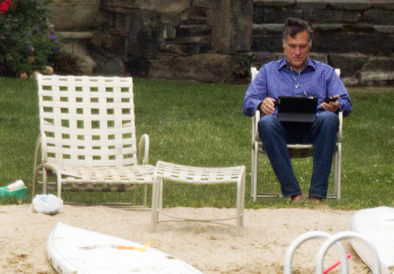 Republican presidential candidate, former Massachusetts Gov. Mitt Romney, earphones in, laptop and mobile phone in hand sits by Lake Winnipesaukee at his home Saturday, July 14, 2012, in Wolfeboro, N.H. (AP Photo/Evan Vucci)