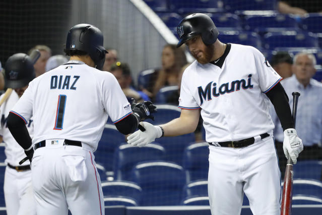 Miami Marlins' Austin Dean, right, congratulates Isan Diaz (1) after Diaz scored on a single by Lewis Brinson during the fourth inning of a baseball game against the Milwaukee Brewers, Thursday, Sept. 12, 2019, in Miami. (AP Photo/Wilfredo Lee)
