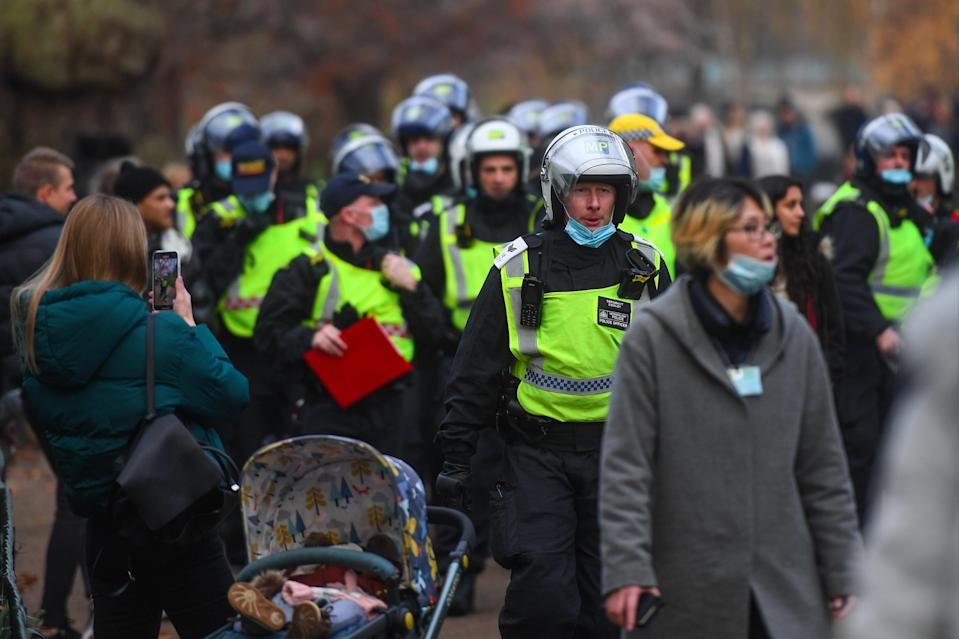 Police officers in riot gear are seen walk through St James' Park in London (Getty Images)
