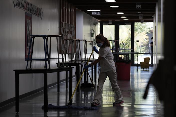 A maintenance worker mops a hallway floor at Torrey Pines High School in San Diego, California, U.S., on Friday, July 10, 2020. (Bing Guan/Bloomberg via Getty Images)