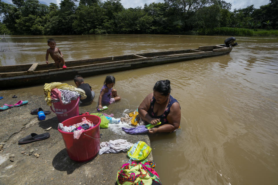 Mariela Lino washes clothes accompanied by her grandchildren on the bank of the Rio Chucunaque, in Penitas, Darien province, Panama, Friday, Oct. 1, 2021. (AP Photo/Arnulfo Franco)