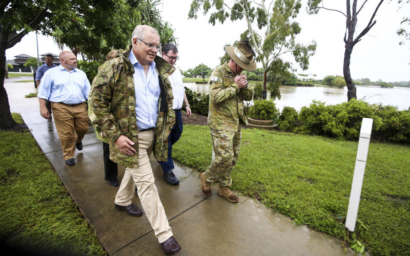 Australian Prime Minister Scott Morrison front and Australian Army Brigadier Scott Winter right visit flood-affected areas in Townsville Australia Tuesday Feb. 5 2019. An estimated 500 homes and business in the city of 230,000 people were flooded