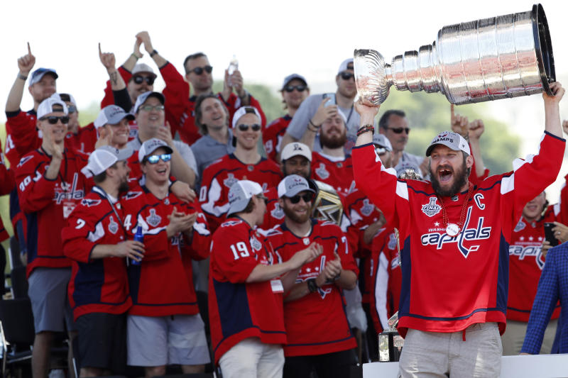 """FILE - In this June 12, 2018, file photo, Washington Capitals Alex Ovechkin, from Russia, right, holds up the Stanley Cup during a victory rally for the Washington Capitals in celebration of winning the Stanley Cup, in Washington. In previous playoffs, a Game 7 at home would've been a """"Here we go again"""" moment of worry for the Washington Capitals. But after exorcising some demons and winning the Stanley Cup last year, the Capitals hope things really are different this time when they host the pesky Carolina Hurricanes in Game 7 on Wednesday night, April 24, 2019.(AP Photo/Jacquelyn Martin, File)"""