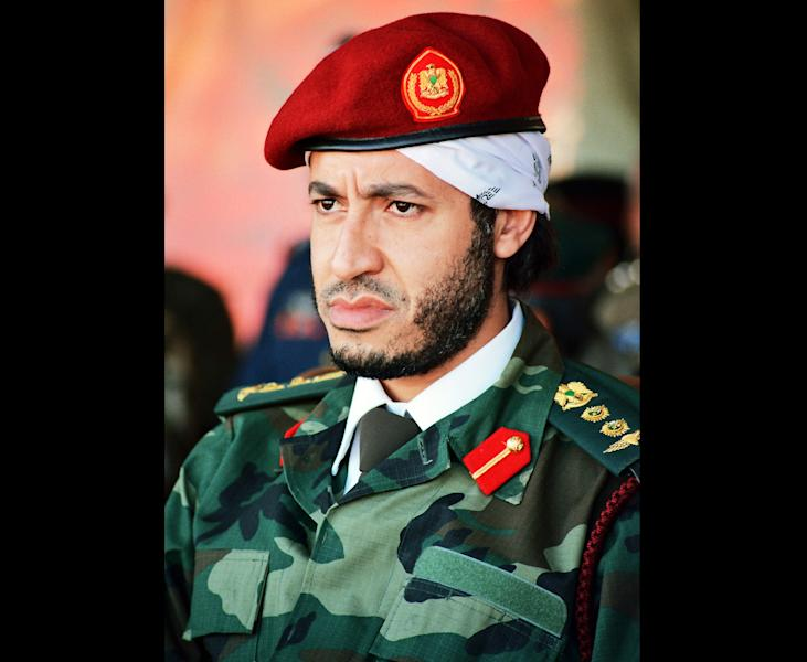 FILE - In this undated file photo made available on Sunday Sept. 25, 2011, al-Saadi Gadhafi, son of the late Libyan leader Moammar Gadhafi, watches a military exercise by the elite military unit commanded by his brother, Khamis, in Zlitan, Libya. Libya says Niger has extradited Moammar Gadhafi's son al-Saadi, who fled as his father's regime crumbled in 2011 and who was under house arrest in the desert West African nation ever since. A Libyan official, who spoke on condition of anonymity in line with regulations, says al-Saadi arrived early on Thursday March 6, 2014 at the Tripoli airport and was transferred to a prison in the capital. (AP Photo/Abdel Magid al-Fergany, File)