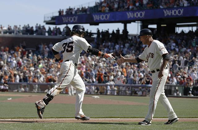 San Francisco Giants' Brandon Crawford (35) is congratulated by third base coach Tim Flannery after hitting a two-run home run off of Atlanta Braves pitcher David Carpenter during the eighth inning of a baseball game in San Francisco, Wednesday, May 14, 2014. The Giants won 10-4. (AP Photo)