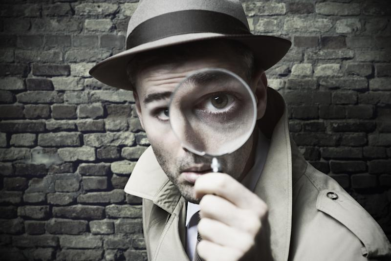 Man in detective hat looking through a magnifying glass