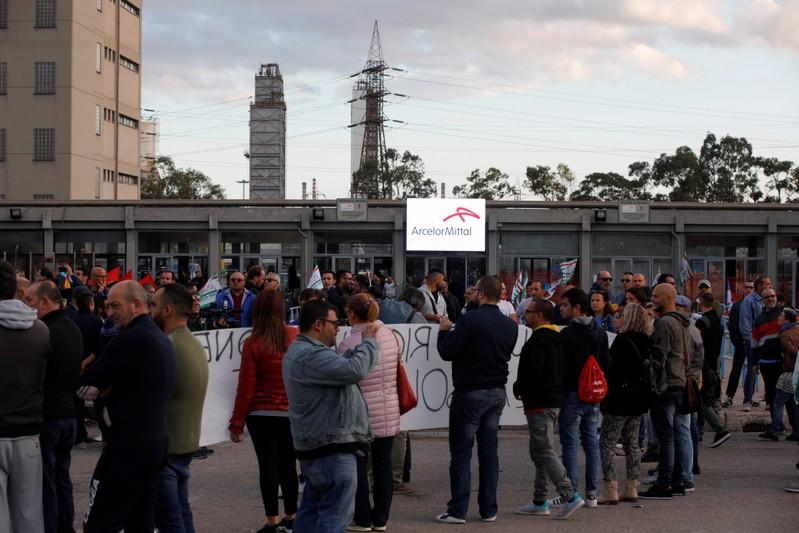 People wait for the arrival of Italian Prime Minister Giuseppe Conte outside the Ilva steel plant, in Taranto