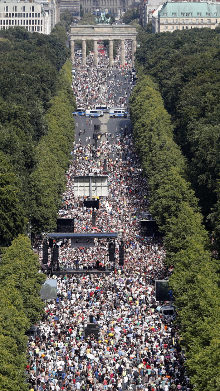 People gather for a demonstration with the slogan 'The end of the pandemic - freedom day' - against coronavirus restrictions in Berlin, Germany, Saturday, Aug. 1, 2020. It comes amid increasing concern about an upturn in infections in Germany. (AP Photo/Markus Schreiber)