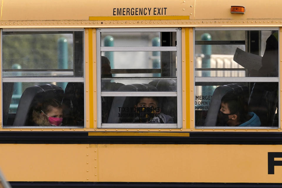 FILE - In this Thursday, Nov. 19, 2020, file photo, elementary school students sit on board a school bus after attending in-person classes at school in Wheeling, Ill. The latest federal relief package includes $81 billion that began flowing to states in late March 2021 with the goal of helping schools reopen quickly. The only problem is many of the school districts' current problems can't be solved by money. (AP Photo/Nam Y. Huh, File)
