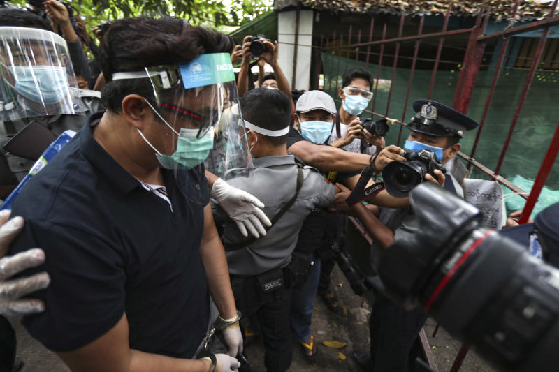 Canadian pastor David Lah, covered with face shield and mask, is escorted by police upon arrival at a township court for his first court appearance Wednesday, May 20, 2020, in Yangon, Myanmar. Pastor Lah attended a court hearing related to charges filed against him for allegedly organizing public Christian activities in Yangon back in April, after the regional government banned mass gatherings in mid-March to curb the spread of the coronavirus.(AP Photo/Thein Zaw)