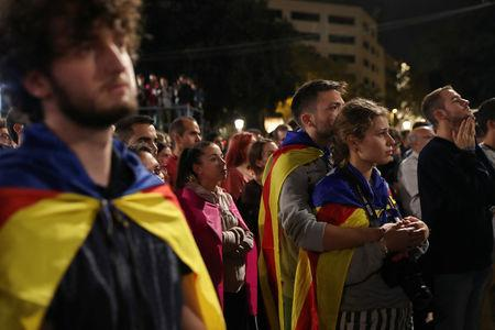 People react as they listen to Catalan president Carles Puigdemont during a gathering at Plaza Catalunya after voting ended for the banned independence referendum, in Barcelona, Spain October 1, 2017. REUTERS/Susana Vera