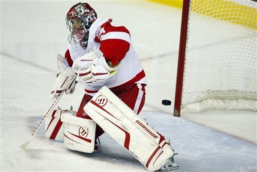 Detroit Red Wings' goalie Ty Conklin looks for the puck as it passes behind him during third period NHL hockey action against the Calgary Flames in Calgary, Alberta, Thursday, Dec. 22, 2011. The Flames won 3-2. (AP Photo/The Canadian Press, Jeff McIntosh)