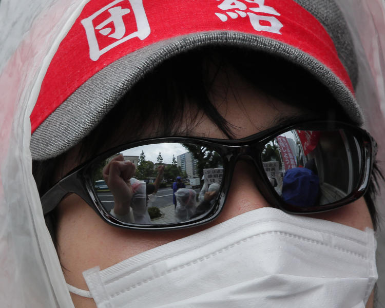 """A demonstrator shouts slogans during a rally, protesting against restarting the Ohi nuclear power plant's reactors in front of the prime minister's official residence in Tokyo, Saturday, June 16, 2012. Japan moved closer to restarting the nuclear reactors for the first time since last year's earthquake and tsunami led to a nationwide shutdown. The headband reads: """"Unite."""" (AP Photo/Itsuo Inouye)"""