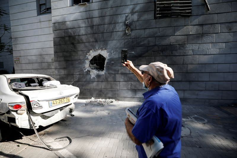 FILE PHOTO: An Israeli man takes a photo with his mobile phone at a residential building after a rocket launched overnight from the Gaza Strip hit it in Ashkelon, Israel