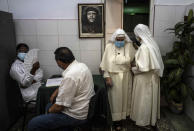 """A framed image of Argentine-born Cuban revolutionary hero Ernesto """"Che"""" Guevara hangs on a wall while nuns leave after being inoculated with a dose of the Cuban Abdala COVID-19 vaccine, in Havana, Cuba, Wednesday, June 23, 2021. (AP Photo/Ramon Espinosa)"""